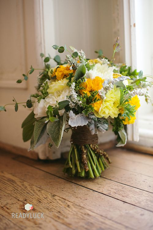 A wedding bouquet with white and yellow roses, dahlias, and greenery | @readyluck | Brides.com