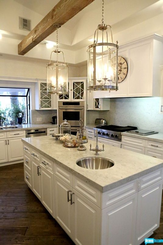 Kyle Richards kitchen @ Home Design Ideas...Love the single wood beam with the beautiful lights hanging down...sweeps your eyes upward in an otherwise all-white kitchen.  Beautiful!