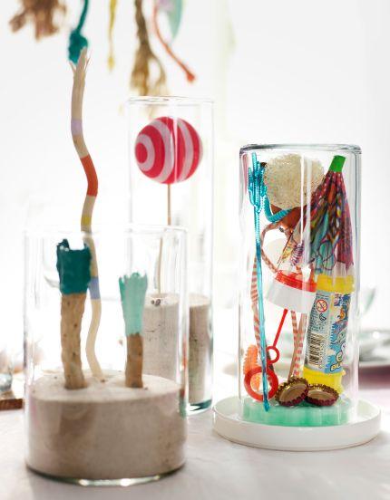 Verzameling van willekeurige strandschatten op tafel, zoals ballen en papieren parasolletjes in glazen bokalen met zand