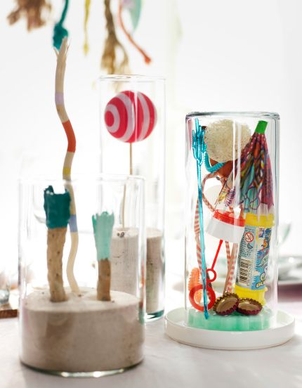 A collection of random beach finds including balls and paper umbrellas inside glass jars with sand in the bottom displayed on a table.