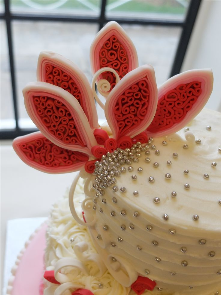 Details of the quilled pink and white wedding cake:  large pink (ombre) flower with silver embellishments.