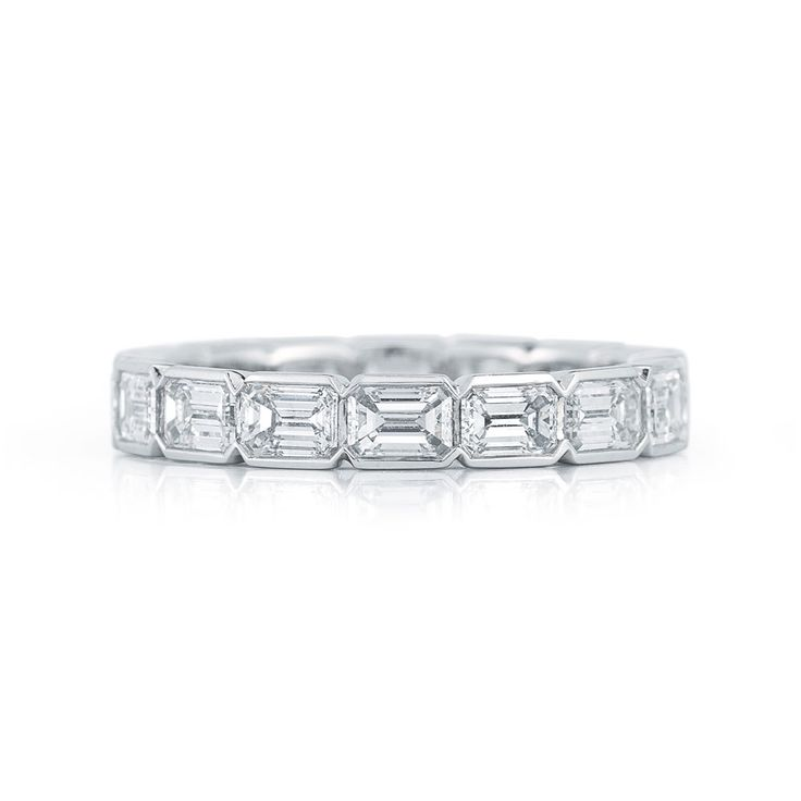 by Kwiat... Emerald cut diamond eternity band in a half bezel setting in platinum    The graceful line of a polished edge embraces chic emerald cut diamonds. The unique design evokes a modern feel creating a brilliant eternity ring.