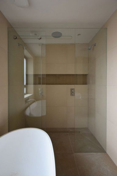 Sliding shower screen installed by Creative Glass Studio in London. Heat soaked glass without metal bar.