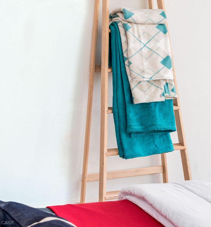 72 produtos bons, bonitos e baratos comprados em home center - A escada de pínus (172,90 reais na Telhanorte) serve de cabideiro para mantas de microfibra. Por 49,90 reais (estampada de casal) e 69,90 reais (lisa queen) no Extra.