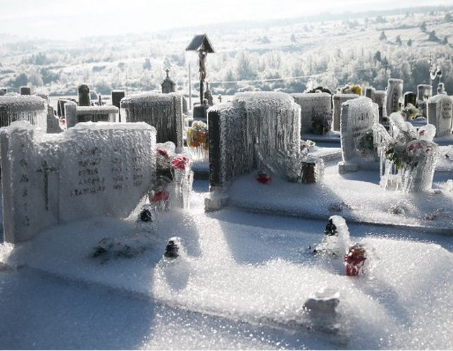 This graveyard is located in Slovenia. It looks frozen because of freezing rain. Freezing rain is rain that falls when surface temperatures are below freezing. It is made entirely of liquid droplets.