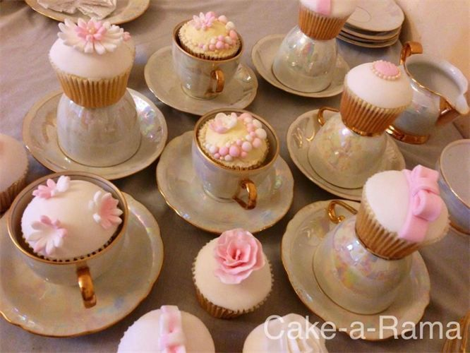 white fondant topped cupcakes hand decorated with pink bows, flowers and buttons  and   tiny edible pearls