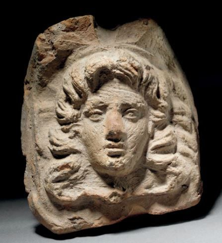 Terracotta antefix, Etruscan, 2nd century B.C. Mould made in the form of a facing head of a youth, with flowing hair, 18 cm high. Private collection