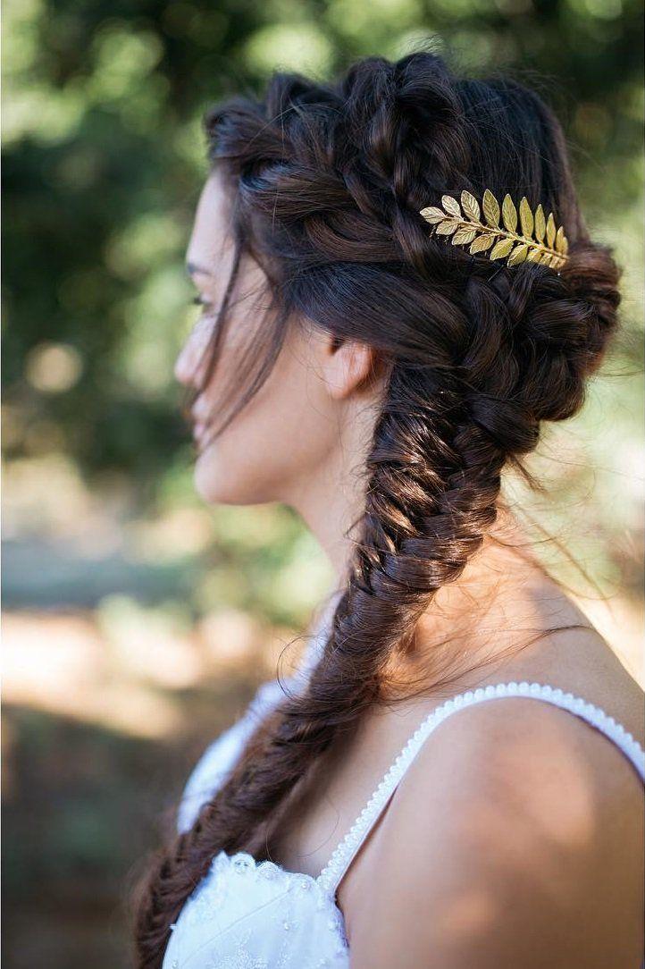 Chica con una trenza cola de pez puesta sobre su hombro y deocrada con una corona de laurel