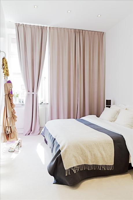 Via Sköna Hem; Heltäckande matta ger hotellkänsla i sovrummet. De generöst tilltagna gardinerna döljer en tråkig vägg och ger illusion av ett större fönsterparti. Säng Sultan från Ikea, bäddad med beige kashmirpläd, Sand, mörkgrått överkast och vita sängkläder, H home, och kuddfodral, Schlossberg/Gertrude.