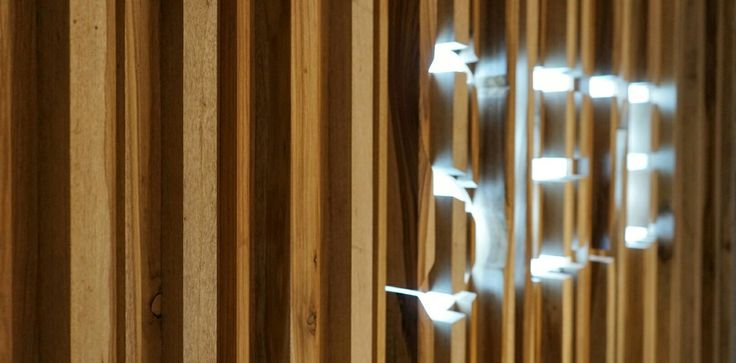 Illuminated cut-trough signage with a wood plank face for a clothing store⚬ Muro de listones de madera con logotipo retro-iluminado para tienda de ropa