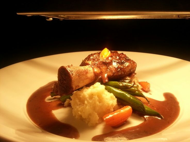 Slow cooked lamb shank served with home made mash potato, local green beans, baby carrots & red wine jus