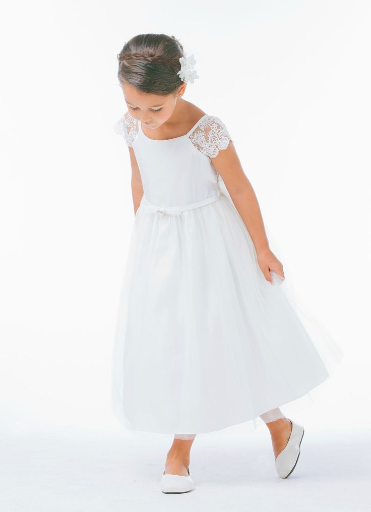 Classic and elegant are the first words that come to mind when we look at this stunning dress. Watch your little one transform into an angel the second she puts it on. This dress is great for a First Communion. We absolutely love the lace trim on the cap sleeves and the delicate pearl brooch on the waist. Fully lined with a zipper back. This dress is made by a local Los Angeles designer that offers styles with vintage detailing and modern appeal that are proudly made in the United States.