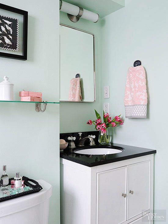 Soft pink accents pick up the energy in this small bathroom that features soothing mint green walls. Black and white finishes, including the vanity countertop, are an ode to the home's 1930s roots./