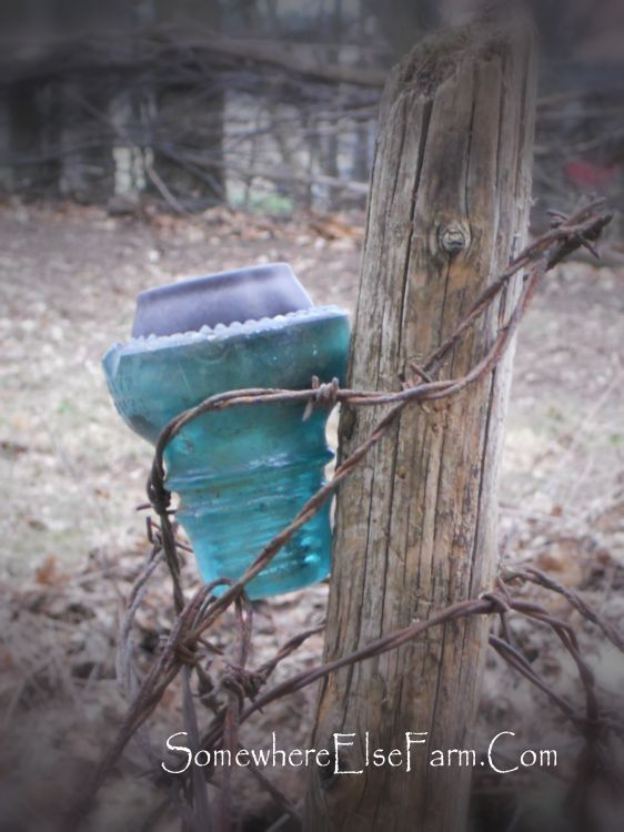 Solar light insulator: hang a telephone insulator by wrapping it with wire (doesn't have to be barbed wire), pop the top off an inexpensive solar light, and put it in the insulator.