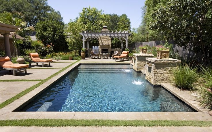 Lap Pool With Stone Columns And Scuppers, Aqua Blue Pebble Sheen, And  Tanning Shelf