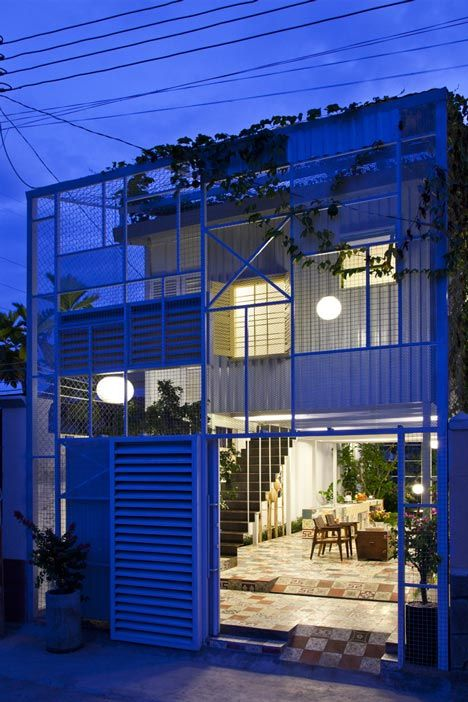 Climbing plants and vines shoot up over a gridded facade of metal beams and panels at this house.