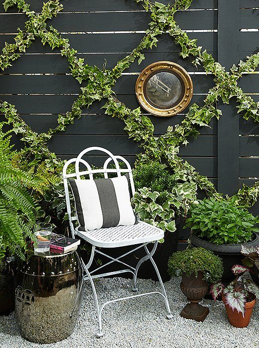 This lush patio garden gets vertical interest from the simple DIY garden trellis behind, which lends a bit of French flair to the space.
