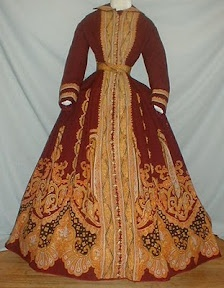 "A truly magnificent 1860's burgundy cashmere wool paisley print dress that has documentation.  The old note reads ""Paisley dress worn by Grandma Eckert at mother's wedding.""  The paisley pattern is designed in shades of orange, blue and black.  The dress comes with it's original paisley print belt. The armscyes and neck are piped.   The bodice is lined with cotton and the lining has a hook and eye closure.  The dress has a front button closure to mid hip area and the rest of the buttons are…"