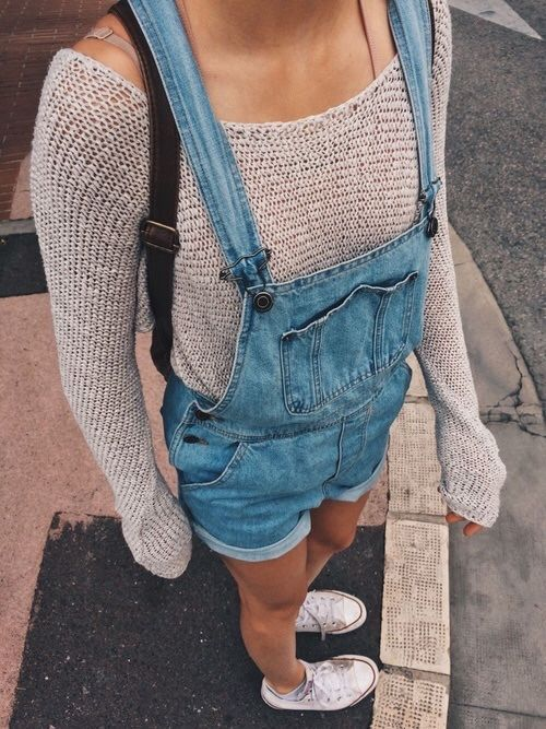 Tan sweater, blue dungaree shorts and black backpack