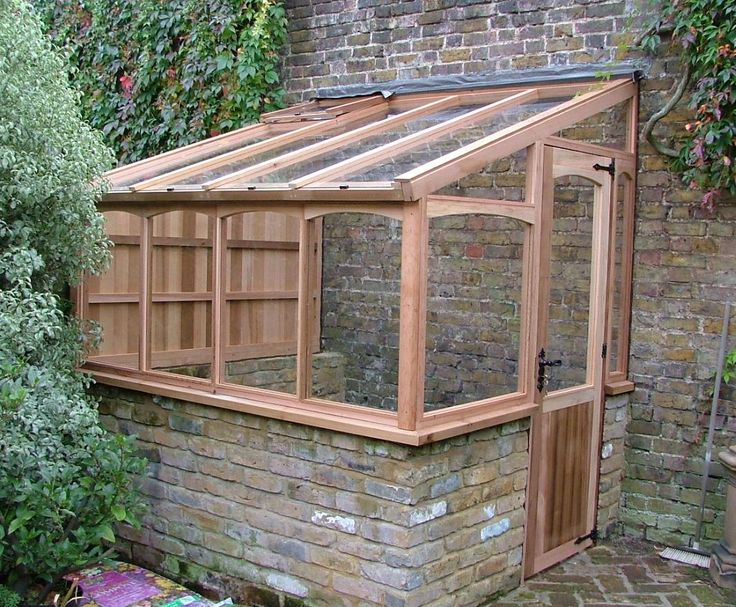 greenhouse built against brick wall for thermal mass.