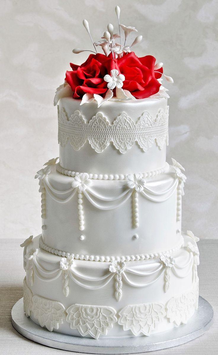 Un model de tort cu iz regal, decorat cu o dantela eleganta si pus in valoare de cativa tradafiri rosii, realizati manual petala cu petala, o varianta potrivita pentru o nunta rafinata.