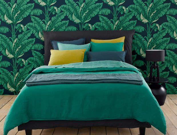 Une parure de lit en lin AM.PML'ambiance de cette chambre est pile dans la tendance. Un papier peint au feuillage exubérant meuble à lui tout seul la pièce. Le linge de lit - en lin lavé légèrement froissé-, décline une palette de bleu et de vert relevée par un jaune lumineux, (housse de couette à partir de 89 €, taie à partir de 24 €).