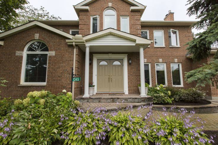 A paving stone walkway leads to the portico entry of this former Kingsmere all brick model home in the heart of Manotick Estates, which is situated on a beautiful lot with gardens and in-ground swimming pool. $799,000.