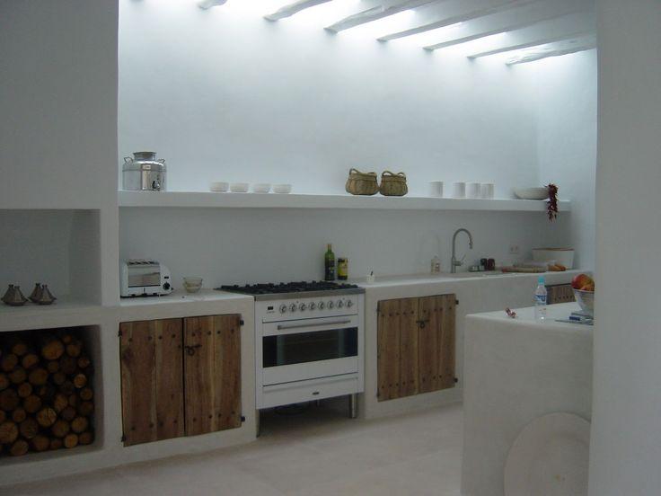Stupenda cucina rustica moderna, semplice e lineare: sportelli in legno grezzo,  pavimenti in travertino e soffitto e pareti dipinte in bianco - piccolo camino aperto