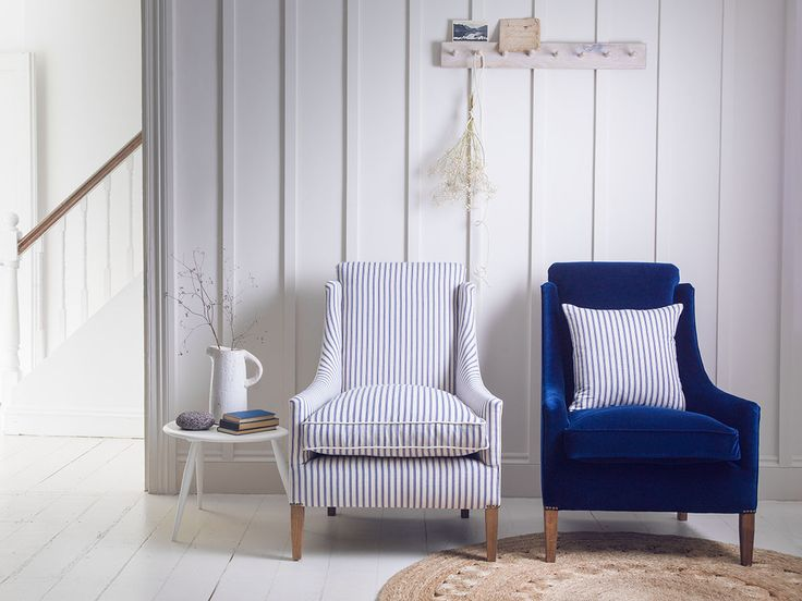 Crisp blue and white ticking stripe chair with plain blue chair and matching striped cushion. The look is kept fresh with white painted floor tongue and groove walls and simple natural rug