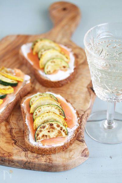 お好みのパンの上に水切りヨーグルトを塗り、スモークサーモンと焼いたズッキーニをのせた手軽にできるおつまみです。