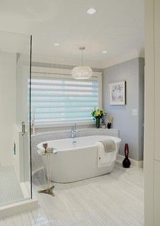 A serene bathroom with beautiful grey tiled floor, freestanding bathtub and chrome details.