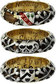 This enamelled gold mourning ring commemorates the death of Samuel Nicholets of Hertfordshire who died on 7th July 1661, as is recorded in the inscription inside the ring. The ring is hollow, and a lock of hair curls around within it, visible through the openwork of the enamelled decoration of skulls and coats of arms.