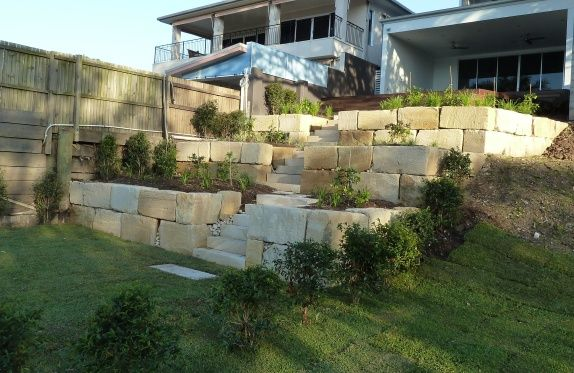 A sandstone retaining wall for erosion control and access to the Brisbane River. It is softened with a mixture of native shrubs and grasses.