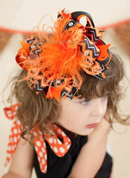 "A bright, zesty, big Halloween hair bow perfect for the fall holiday season! Citrus colored ostrich feathers gather with chevron pattered ribbons in hues of tangy orange, and licorice black and white. Pretty jewels literally pop! Cheeky, zany, and oh so fun! Select from several accessory options including: alligator clip, french clip, or soft crochet headband of your choice.  -available in 4"", 5"" or 6"" size -for all ages including babies and big girls -bow can be worn with or without…"