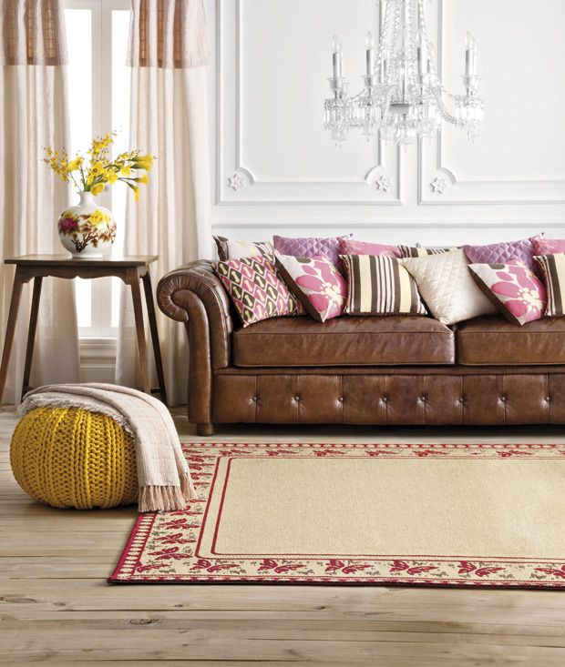Tan Leather Chesterfield Sofa With Pink And Brown Cushions, Yellow Knitted  Pouf, Red And Cream Rug
