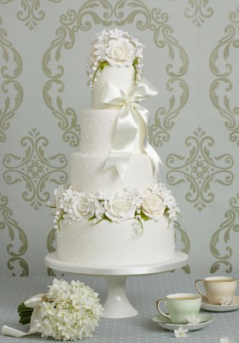 Amelie...The ivory icing is covered in tiny white dots all over, whilst the top and bottom tier are crowned with an abundance of hand-crafted sugar roses, lily of the valley sprays and paper whites