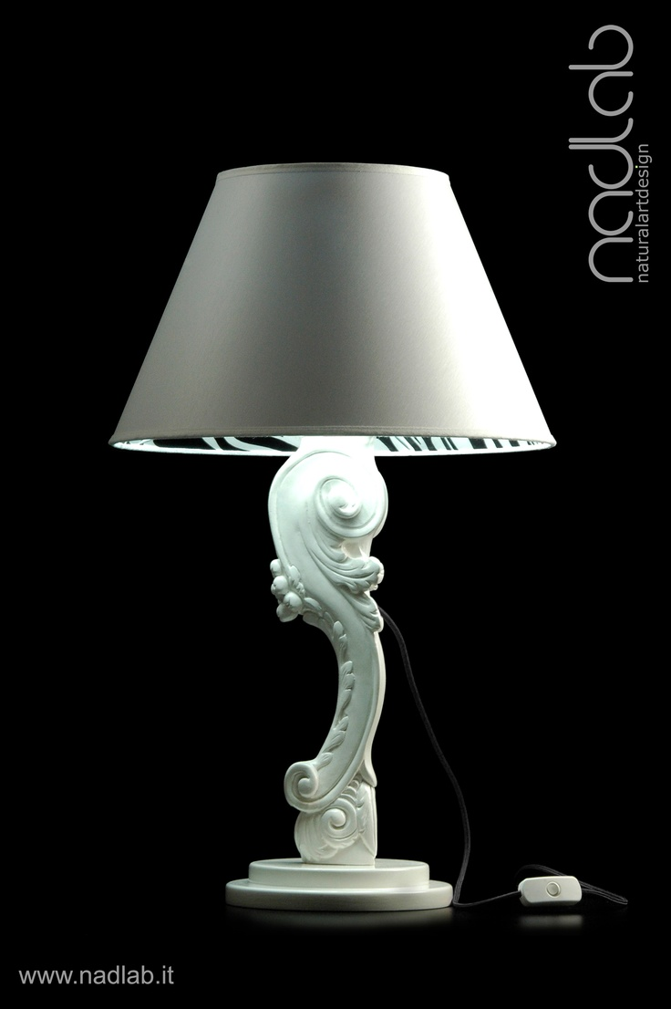 Bucefalo zebra edition (light ON)  The base and the body of the lamp in wood are hand-carved.  The lampshade is made of PVC and coated in white chinette lined in zebrated pure silk.  Decorated in white gloss.  Customizable on request.