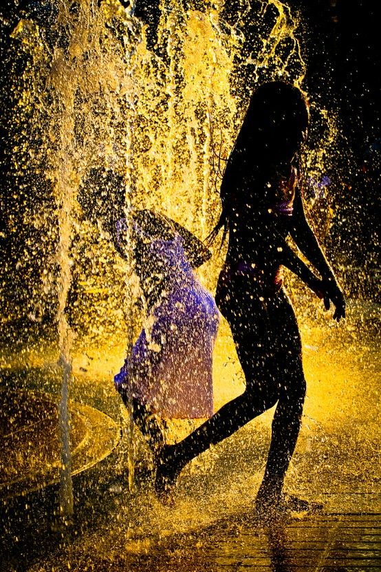Girls dancing in a fountain.