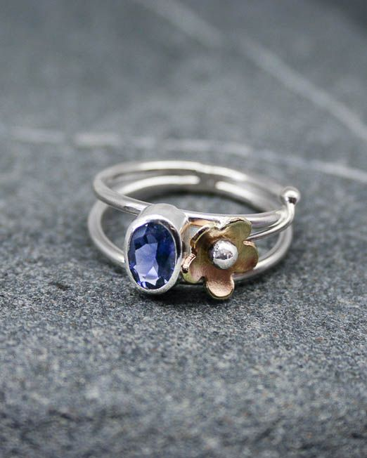 Unique handmade silver Iolite flower ring with brass daisy shoulder.  The ring features a single oval 7x5 oval facetted iolite which is set in a bezel type setting, to one side is a single brass daisy with silver stem, all resting on a double, round wire band.  Available with several other gems, quote on request.  #Daisy #Floral #Gemstone #HandmadeJewellery #MixedMetal #Ring #Silver #Starboard