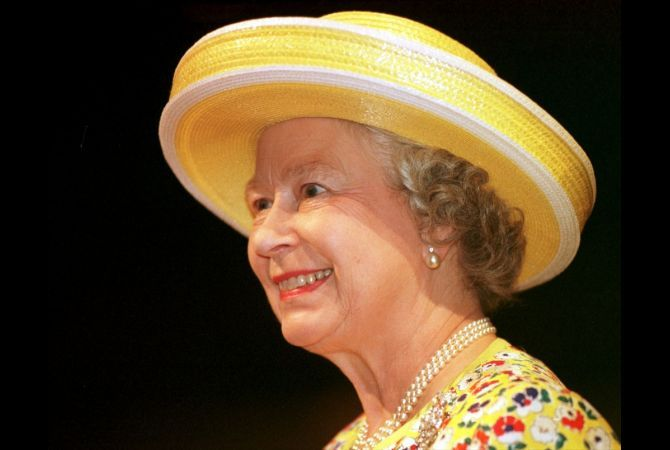 """Queen Elizabeth II smiles at the Stratford Theater as actors perform the wedding scene from Shakespeare's """"The Taming Of The Shrew"""" in in Stratford, Ontario, on June 28, 1997."""