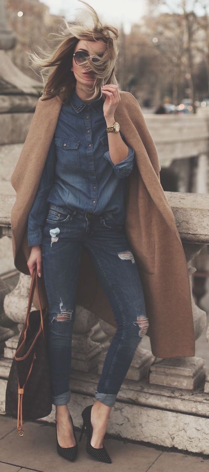 Fall / Winter - street chic style - denim on denim - denim shirt + dark denim ragged skinnies + black suede stilettos + camel long coat + brown handbag + aviators
