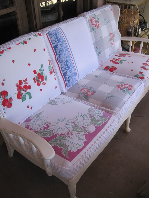 Vintage re-do of a solid wood couch, repainted white and re-upholstered with tablecloths and chenille bedspread
