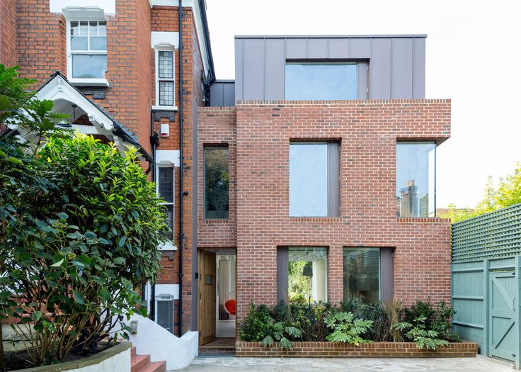Alexander Martin Architects has added a three-storey extension to a Victorian house in London, featuring brick walls and a big window facing the garden