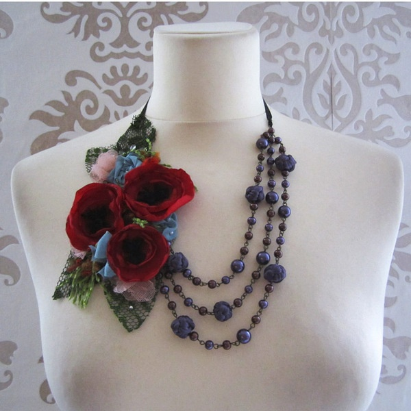 This statement necklace is handsticthed with handmade poppy flowers, dusty blue silk rosette, assorted beads, tulle and other whimsies. The pallett...