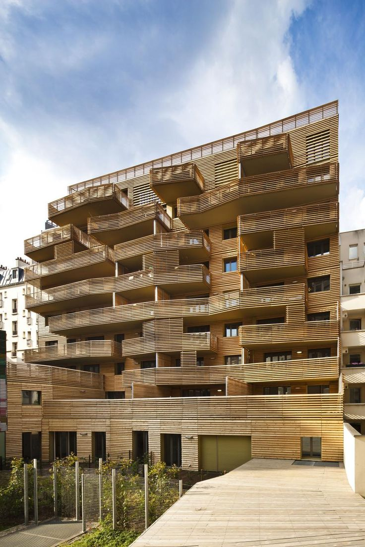The south-facing rear of the apartment with timber slats protruding balconies overlook a large communal garden