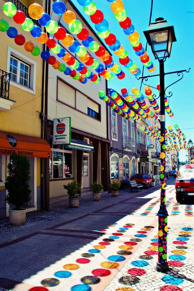 Streets in Águeda, Portugal have been covered in a colorful canopy of umbrellas and beach balls for the month of July in a recurring summer installation by Portuguese art studio Sextafeira Produções. The studio has created the installation each summer since 2012.