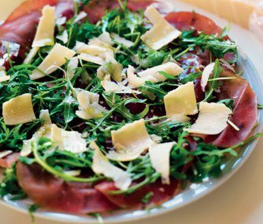 Bresaola e rucola är inget mindre än en underbart smakrik sallad med lufttorkat nötkött, parmesanost och citronjuice. Sältan från rucolan, parmesanen och bresaolan bryts av mot den syrliga citronen och salladen toppas med olivolja.