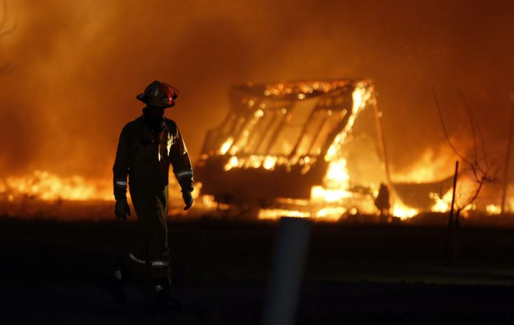 Oklahoma fires...A firefighter walks past a burning mobile home at a mobile home park near Prairie Grove Rd. and Douglas during Oklahoma wildfires in south Logan County, Sunday, May 4, 2014.