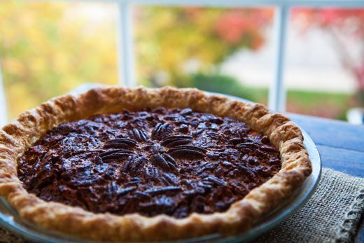 Traditional pecan pie recipe using fresh pecans, molasses, corn syrup, brown sugar, and eggs.
