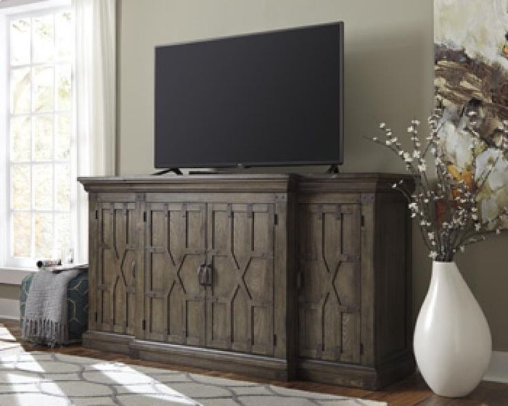 Extra Large TV stand or console dark wood with details. by Herb Hays Furniture; Ashley Furniture in Hopkinsville, KY.